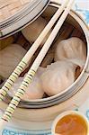 Dim sum in bamboo steamer, sauce beside it (Asia)