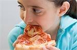 Little girl eating slice of pizza