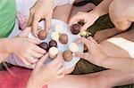 Les mains des enfants atteignant des guimauves enrobées de chocolat