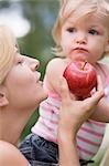 Mère offre jeune fille une pomme rouge