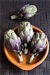Quatre bébés artichauts avec plat de terre cuite