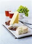 Des fromages avec craquelins, noix, raisins, bière