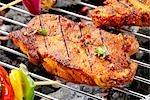 Pork neck steaks on barbecue