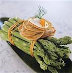 Blinis avec crème sure et de caviar sur asperges vertes