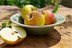 Pommes entières sur une plaque, la moitié d'une pomme à côté de la plaque