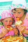 Deux enfants manger des pizzas sur la plage