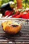 Pommes de terre grillées sur le barbecue, légumes en arrière-plan