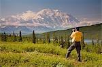 Male tourist views Mt.McKinley & Alaska Range near Wonder Lake Denali National Park Alaska Summer