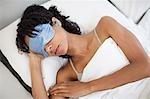 Femme allongée dans le œil masque et oreilles bouchons