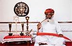 Man holding a sword and smoking, Meherangarh Fort, Jodhpur, Rajasthan, India