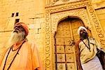 Vue d'angle faible de deux sadhus debout devant un bâtiment, Jaisalmer, Rajasthan, Inde