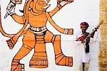 Mid adult man playing sarangi in front of a wall, Jaisalmer, Rajasthan, India