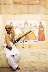 Mature man playing sarangi in front of a wall, Jaisalmer, Rajasthan, India