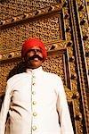 Homme mûr, debout devant une porte d'un palais, City Palace, Jaipur, Rajasthan, Inde