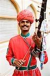 Mid homme adulte jouant sarangi dans un palais, City Palace, Jaipur, Rajasthan, Inde