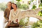 Tourist Couple sitting on wall by Stone Bridge, Granada, Spain, portrait