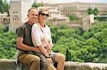 Tourist Couple sitting on Wall in Granada, Spain, portrait
