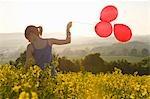 Girl walks thru field with balloons