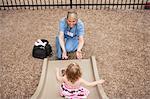 Nurse Catching Child on Playground Slide