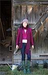 Teenage girl by rustic barn