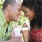 Nahaufnahme von Mitte erwachsener Mann und eine junge Frau hält Gläser milkshake