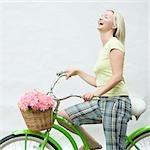Profil de côté d'une femme adulte moyen sur une bicyclette et rire