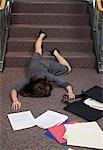 Femme d'affaires tombant, paperasserie dispersé