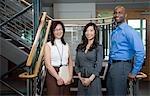 Portrait des collaborateurs heureux dans la cage d'escalier de bureau