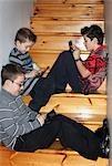 Trois jeunes garçons jouant sur des consoles de jeu vidéo