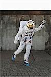 An astronaut on a city sidewalk pretending to take off in flight