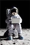 Un astronaute sur la lune, assis sur un rocher à l'aide d'un ordinateur portable