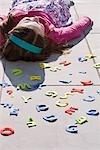 A girl lying down behind felt alphabet letters