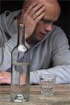 Einen Mann betrunken und deprimiert mit einer Flasche Wodka und ein leeres Glas