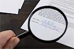 Die Unterschrift auf einen Mietvertrag mit einer Lupe untersuchen