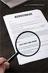 Das Kleingedruckte der einen Arbeitsvertrag mit einer Lupe untersuchen