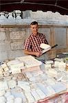 Homme à l'étal de marché de fromage de brebis en france