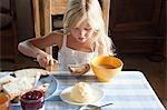 Mädchen, die Verbreitung von Butter auf Brot