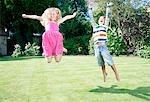 Children jumping in backyard