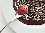 Gros plan de la fraise sur cuillère au-dessus de bol de chocolat fondu