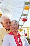 Senior couple s'enlaçant au parc d'attractions