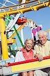 Souriant couple senior sur le tour de parc d'attractions