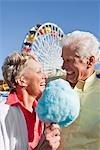 Senior couple partage de barbe à papa au parc d'attractions le sourire