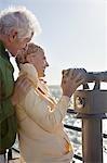 Smiling senior couple using coin-operated binoculars