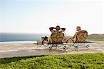 Senior couple on lounge chairs on patio overlooking ocean