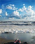 Turnschuhe am Strand mit rauen Wasser