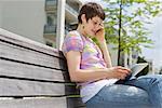 Jeune femme avec un téléphone portable et l'iPad sur un banc