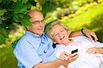 Happy senior couple with smartphone in garden