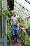 Jardinier s'élève à effet de serre en tenant la plante en pot