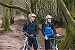 Couple on mountain bikes in woods