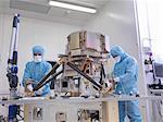 Workers assembling satellite dish